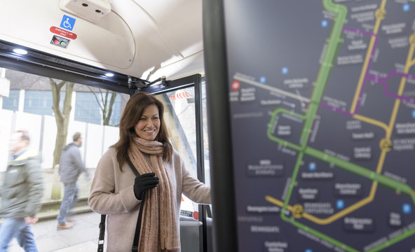 Passenger paying for ticket on electric bus