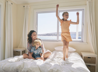 Mother and son watching girl jumping on bed