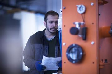 Engineer holding paperwork operating control panel