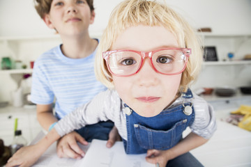 Portrait of cute girl in eye glasses with brother in kitchen