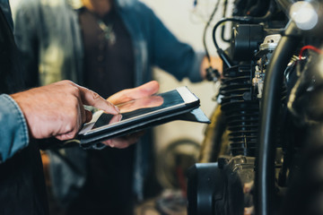 Two mature men, working in garage, using digital tablet, close-up