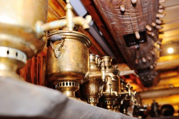 Antique samovars on a shelf on a wooden background