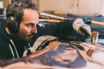 Metalworker hammering copper in forge workshop