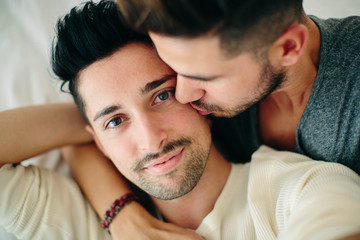 Portrait of male couple, man kissing partner on cheek