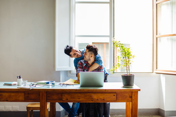 Male couple at home, man sitting at table using laptop, partner hugging him