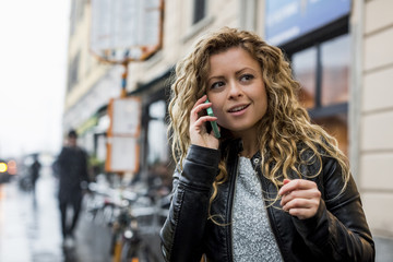 Woman in street making telephone call on mobile phone