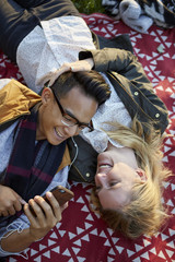 Overhead view of couple on picnic blanket sharing earphone music