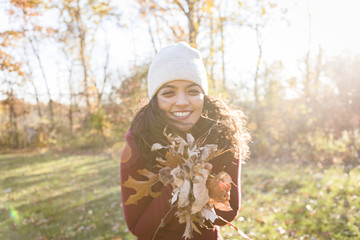 Portrait of young woman holding autumn leaves