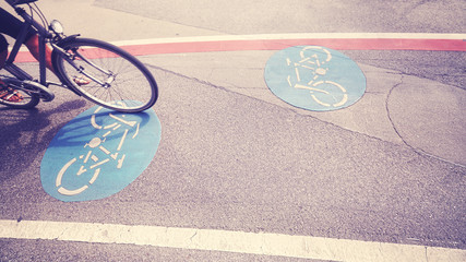 Vintage toned bicycle lane with front part of a bike in motion.