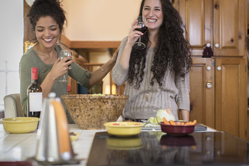 Two female friends preparing salad and laughing at kitchen counter