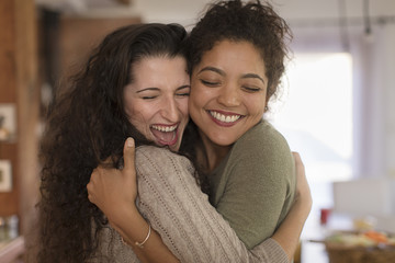 Two young women friends hugging in kitchen