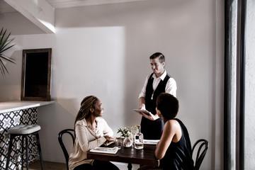Waiter serving diners in restaurant, waiting using digital tablet