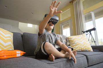 Young boy sitting cross legged on sofa, wearing virtual reality headset, hands reaching out in front of him