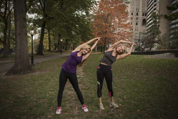 Two mature female friends training in park, bending over sideways