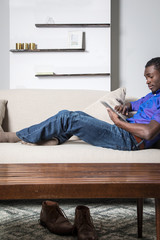 Young man relaxing on sofa, using digital tablet