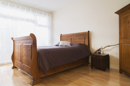 Antique wooden queen size sleigh bed in master bedroom of renovated ground floor apartment in old residential cottage style home