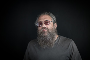 Portrait of mature man with beard, against black background