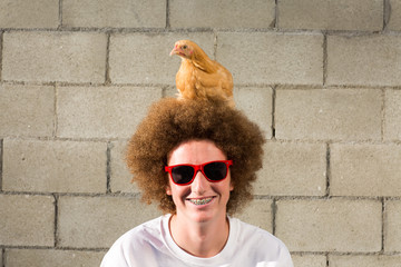 Portrait of teenage boy with red afro hair, chicken sitting on head