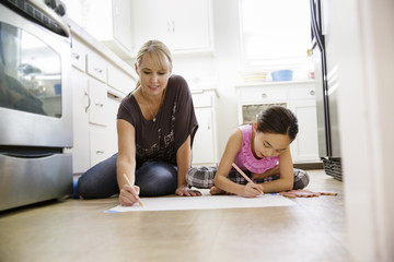 Mother and daughter sitting on kitchen floor drawing