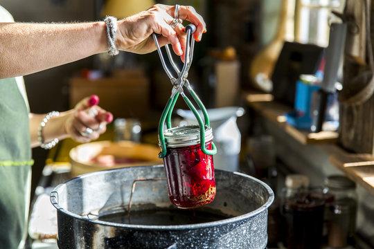 Woman's hands inserting beetroot preserves jar into saucepan