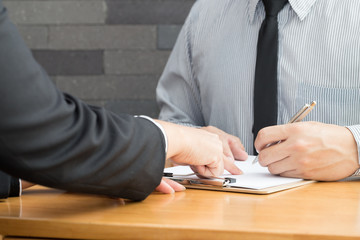 Two business partners signing contract in document