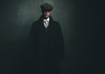 Mysterious retro 1920s english gangster with flat cap and black coat.