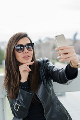 Portrait of a young attractive woman making selfie photo on smartphone