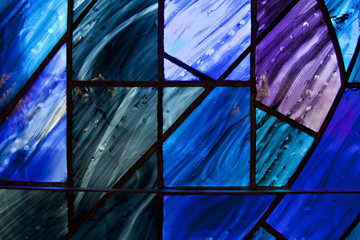 Beautiful shades of deep blue and purple on uniquely shaped stained glass window.