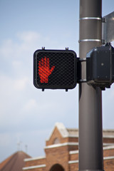 Electronic crosswalk sign with warning hand signal.