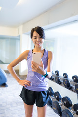Woman taking selfie in front of mirror in gym