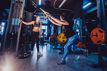 Young adult girl doing suspension rope exercise together with her personal private coach.