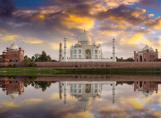 Wall Mural - Taj Mahal at sunset as seen from the Yamuna river banks with moody sky. Taj Mahal designated as a World Heritage Site is a masterpiece of Indian heritage and architecture.