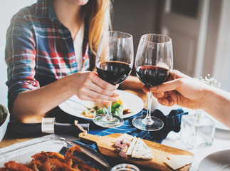 Young romantic couple celebrating with glasses of red wine, Happy couple making cheers at restaurant, cozy atmosphere, holidays and enjoyment concept