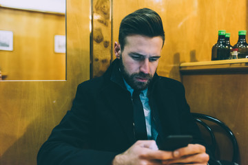 Young contemporary businessman using smart phone