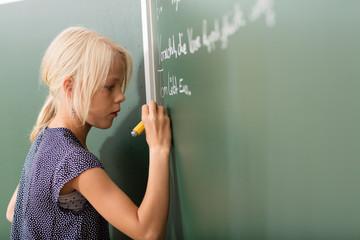 Mädchen schreibt mit Kreide an die Tafel