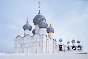 View of the Assumption Cathedral and the bell tower from behind the wall of the Rostov Kremlin in winter.