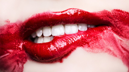 Passionate red lips. Blurry makeup up close. Biting lip. Macro photography, small depth of field