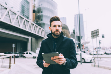 Young bearded businessman outdoor using tablet
