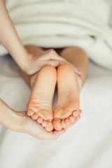 Masseur massaging little baby's foot, shallow focus
