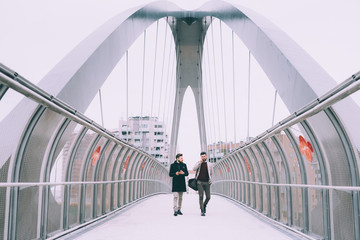 Two young businessman smart phone outdoor walking