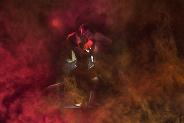 Young caucasian couple dancing tango in a burning room . Red backlight, low key image.