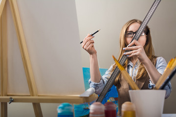 Student of art school. A woman paints a painting on canvas. A blonde in glasses uses a ruler.