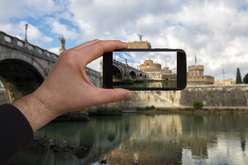 smartphone in hand photographing the city of Rome at sunset - these are all photographs made by me, which separately can be found on my portfolio fotolia