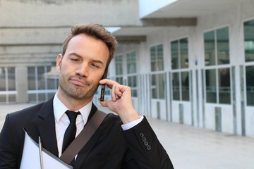 Man crossing his eyes annoyed on the phone