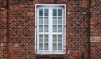 Vergittertes Fenster eines Backsteinhauses