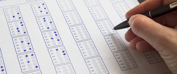 Filling exam questionnaire,hand with pen marking right answers at school or university