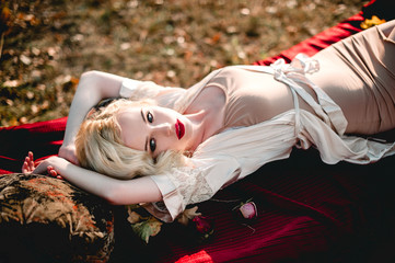 Beautiful and elegant blonde woman with red lips and hair waves wearing beige nightie posing on the bed outdoors autumn, retro vintage style and fashion. Retouched fine art toning shot
