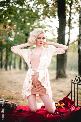 Beautiful And Elegant Blonde Woman With Red Lips And Hair Waves Wearing Beige Nightie Posing On