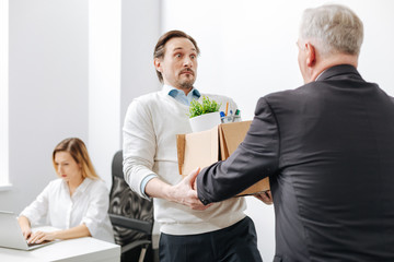 Astonished employee receiving the box with belongings from the employer