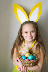 Pretty little girl, dressed in Easter bunny ears, holds basket with colored eggs